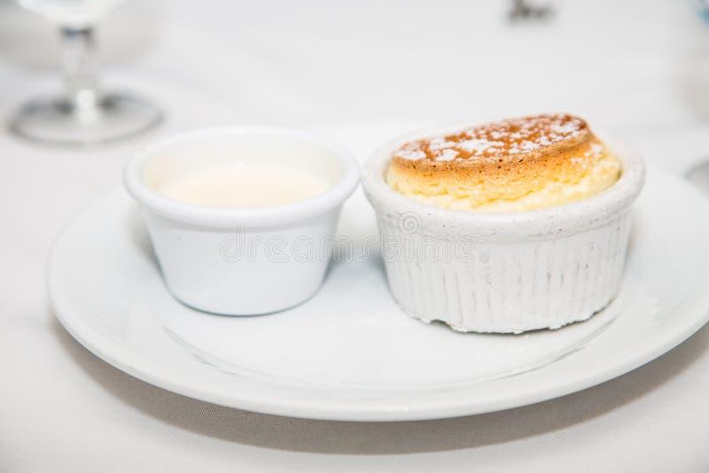 Горячее испеченное суфле с ванильным соусом на плите стоковая фотография