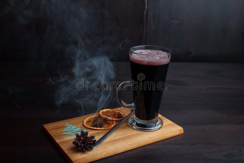 Горячее очень вкусное пряное обдумывало красное вино гарнированное с высушенными оранжевыми кусками и тлея рему на деревянной дос стоковая фотография rf