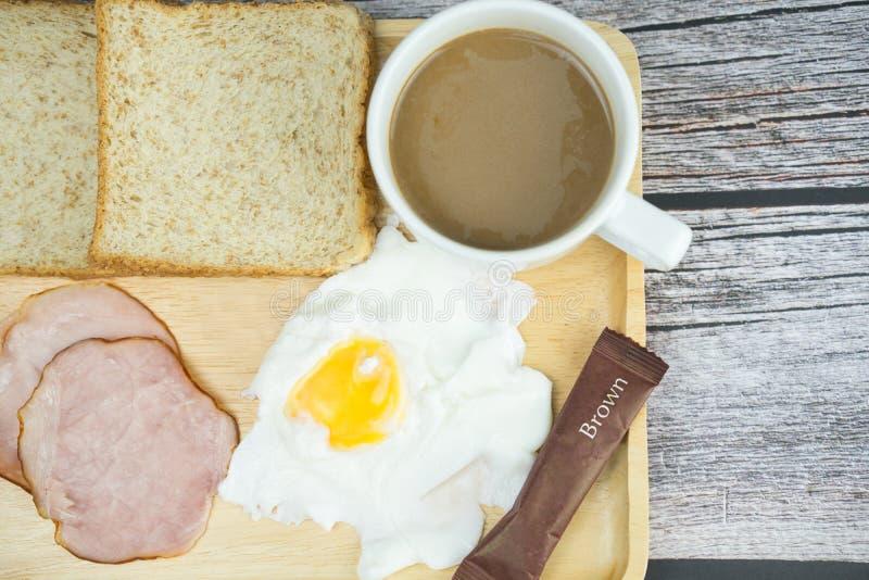 Горячие кофе, яйцо, ветчина и хлеб на деревянном столе на завтрак стоковое фото rf