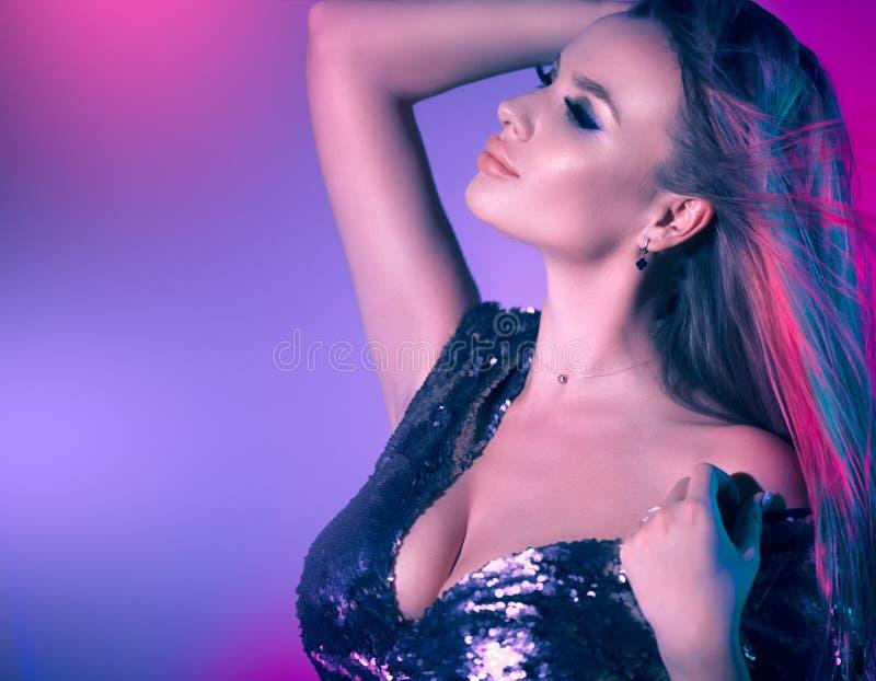 Горячие модельные танцы девушки в УЛЬТРАФИОЛЕТОВЫХ неоновых светах Партия диско Сексуальная молодая женщина с длинными танцами во стоковое фото rf