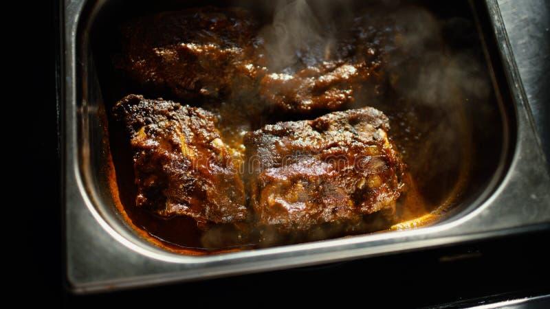 Горячие мясные блюда с нервюрами свинины с соусом подливки кипя на кухне ресторана стоковое фото