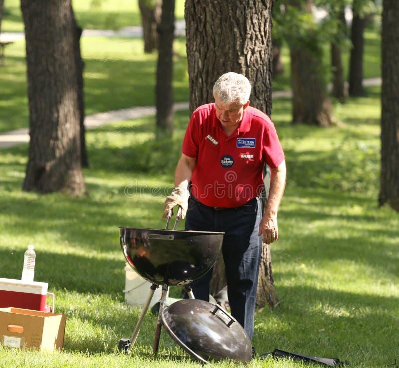 Горячие сосиски барбекю человека на ралли чаепития стоковое изображение rf
