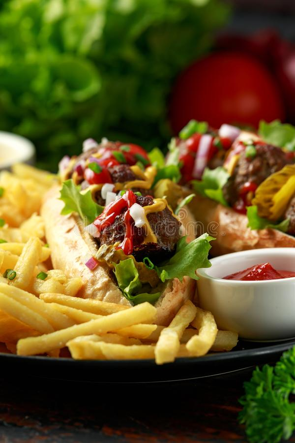 Горячие сосиски шариков мяса с французским картофелем фри картошки, обломоками, crinkle отрезали корнишоны, кетчуп и мустард фаст стоковое изображение