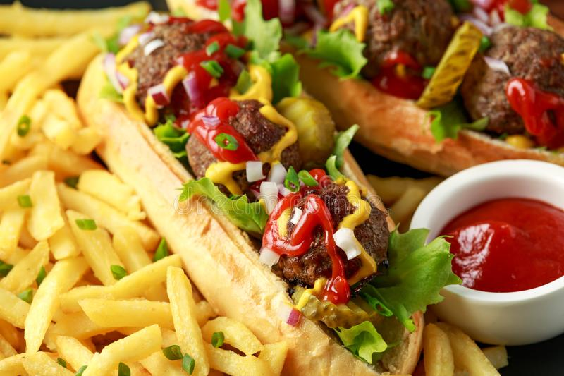 Горячие сосиски шариков мяса с французским картофелем фри картошки, обломоками, crinkle отрезали корнишоны, кетчуп и мустард фаст стоковое изображение rf