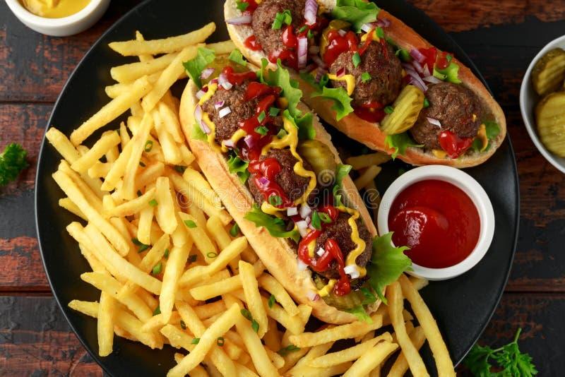 Горячие сосиски шариков мяса с французским картофелем фри картошки, обломоками, crinkle отрезали корнишоны, кетчуп и мустард фаст стоковое фото