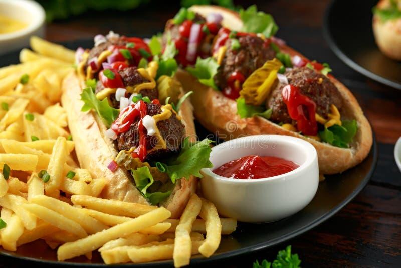 Горячие сосиски шариков мяса с французским картофелем фри картошки, обломоками, crinkle отрезали корнишоны, кетчуп и мустард фаст стоковая фотография