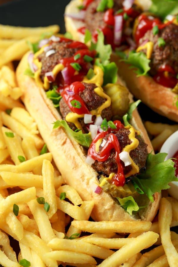 Горячие сосиски шариков мяса с французским картофелем фри картошки, обломоками, crinkle отрезали корнишоны, кетчуп и мустард фаст стоковые изображения rf