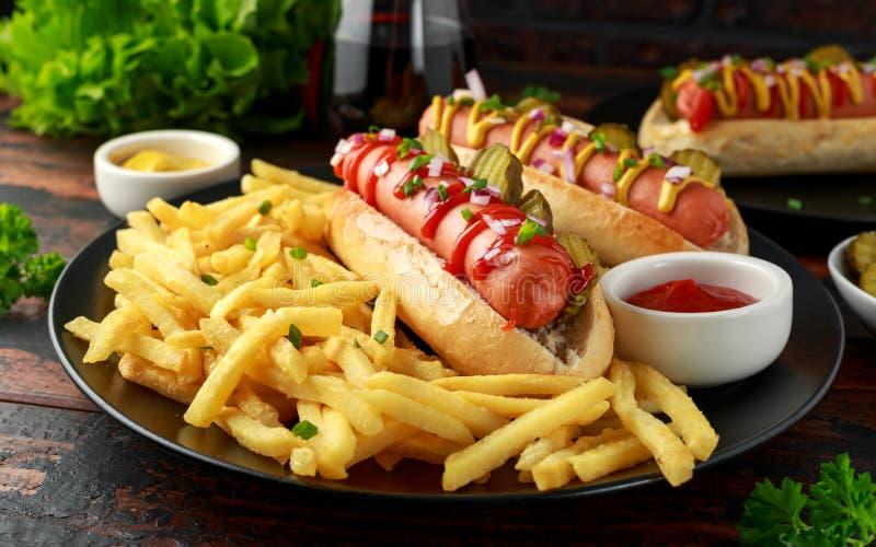 Горячие сосиски сосиски Frankfurter с французским картофелем фри картошки, обломоками crinkle отрезанные корнишоны, кетчуп и муст стоковое фото