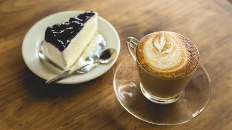 Горячие latte кофе и чизкейк голубики на деревянном столе стоковая фотография