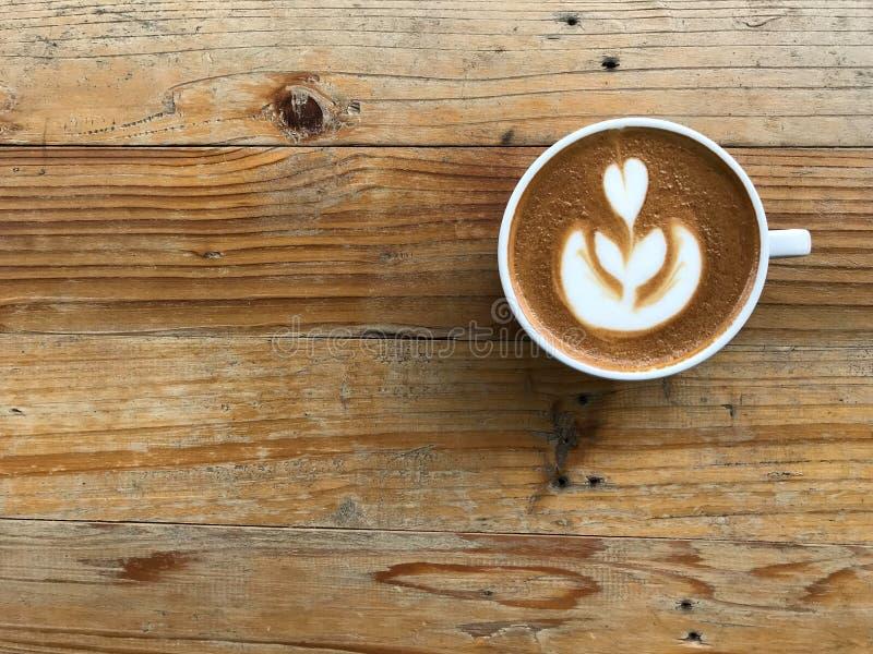 Горячий капучино кофе с красивым латте-артом, поставленный на природный коричневый и ретро-узорный деревянный стол стоковое фото