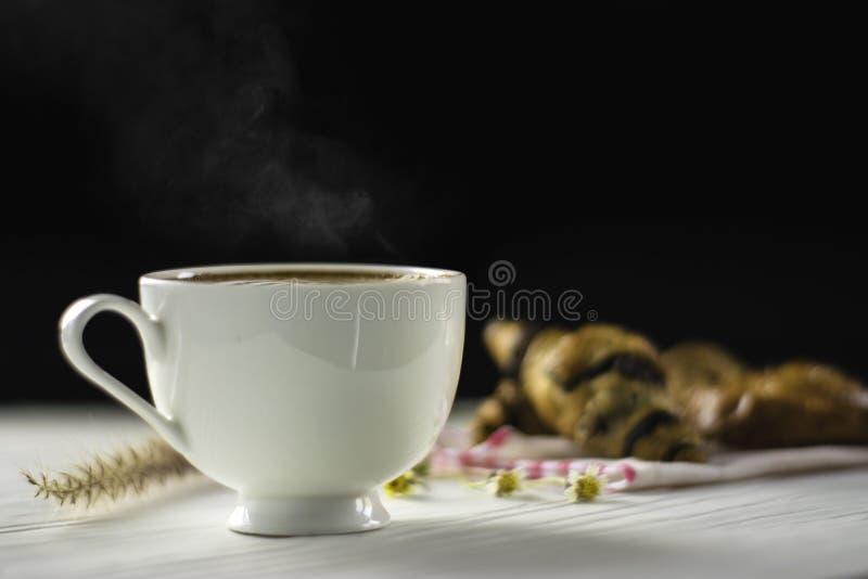 Горячий кофе в белой чашке, с дымом и пекарней помещенными на белой деревянной таблице, темная предпосылка с солнечностью в утре, стоковые фотографии rf
