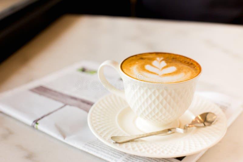 горячий кофе искусства latte с газетой на деревянном столе, годе сбора винограда и стоковые фото