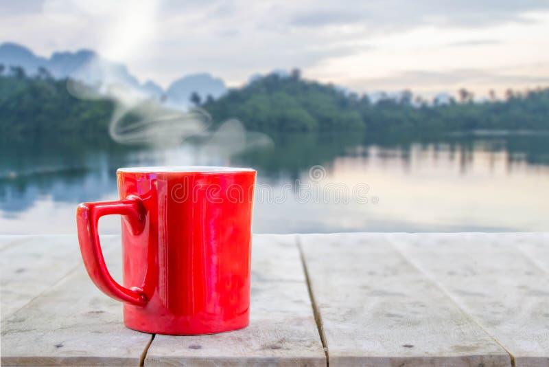 Горячий кофе с белым дымом в красной чашке на деревянной таблице стоковые фото