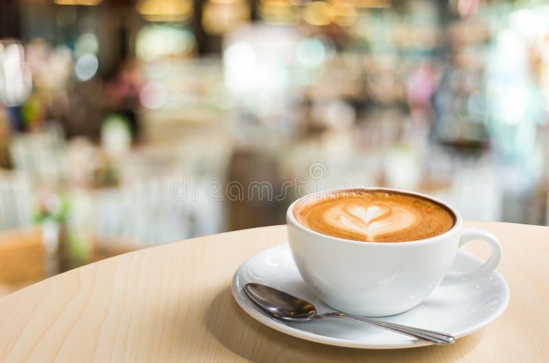 Горячий кофе Latte искусства в чашке на деревянном столе и кофейне bl стоковые фото