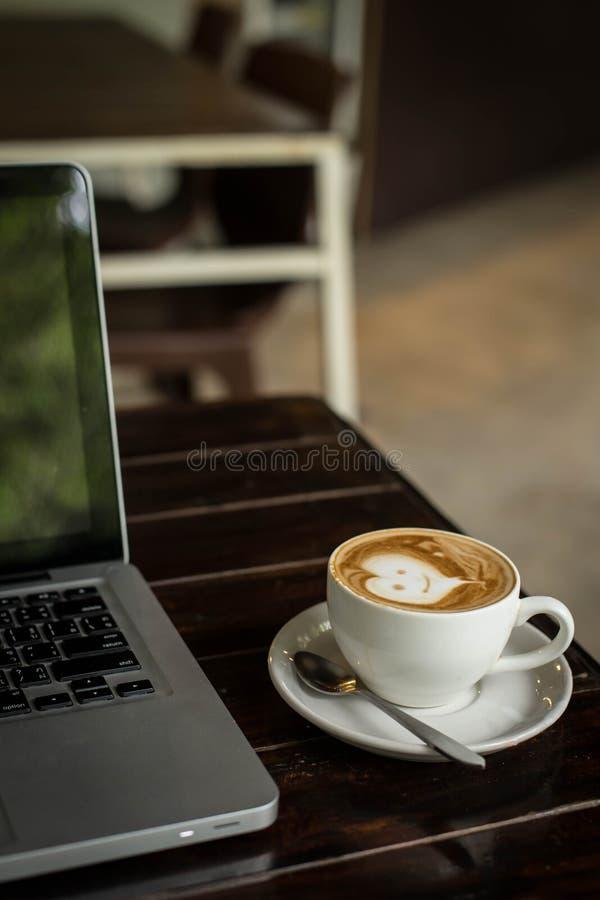 Горячий кофе Latte искусства в чашке на деревянном столе и кофейне bl стоковое фото