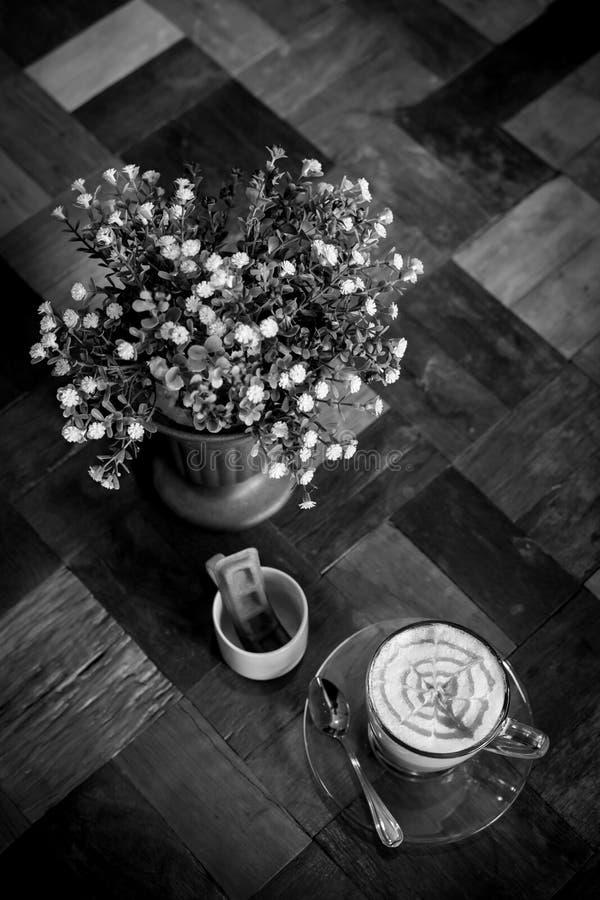 Горячий кофе Latte искусства в чашке на деревянном столе, черно-белом e стоковая фотография