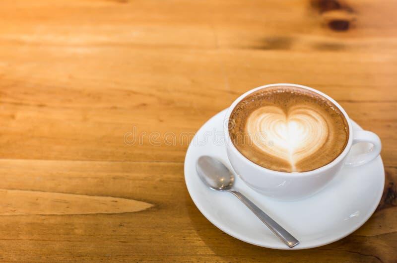 Горячий кофе Latte искусства в чашке на деревянном столе стоковое фото rf