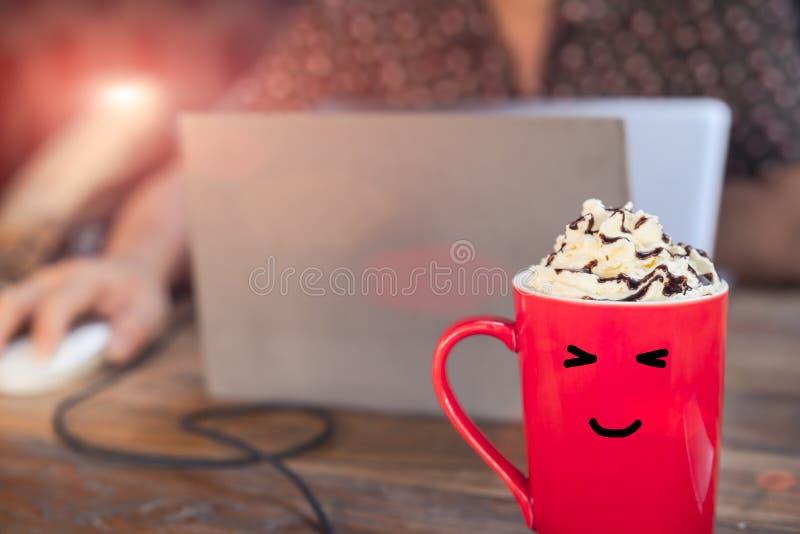 Горячий кофе mocha в красной чашке с стороной улыбки на деревянном столе при деятеля используя компьтер-книжку стоковые фото