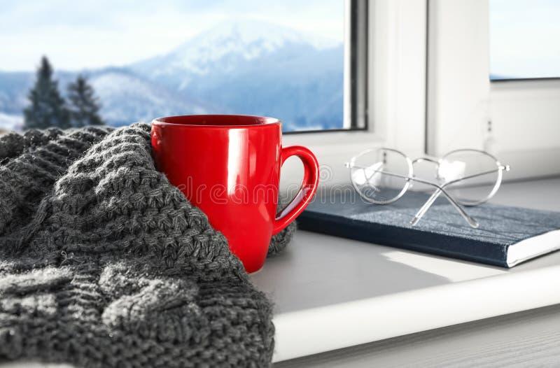 Горячий напиток зимы, шарф, стекла около окна с взглядом ландшафта горы стоковые фото