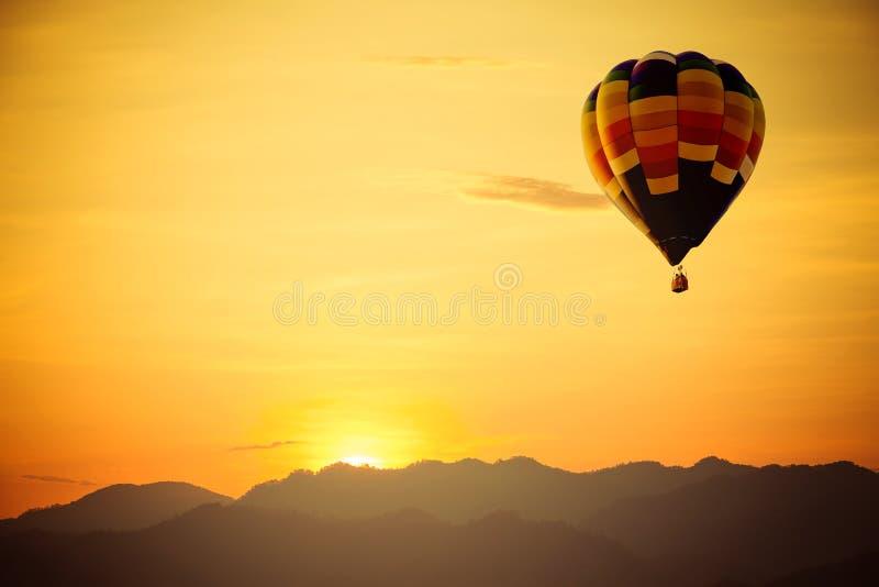 Горячий полет воздушного шара над горой с заходом солнца стоковое фото rf