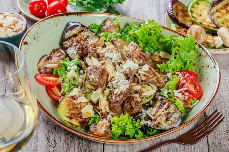 Горячий салат с телятиной, грибами, листьями салата, баклажаном, цукини, томатами, гарнированными с заскрежетанными миндалинами и стоковое фото rf
