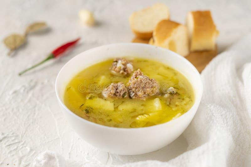 горячий свежий кипеть суп с фрикадельками и картошкой с хлебом на белой таблице, вкусными обедающими стоковое фото