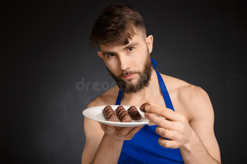 Горячий сексуальный нагой красивый человек с шоколадами, конфетами шоколада Усмехаясь нагой красивый человек нося синюю рисберму  стоковые фото