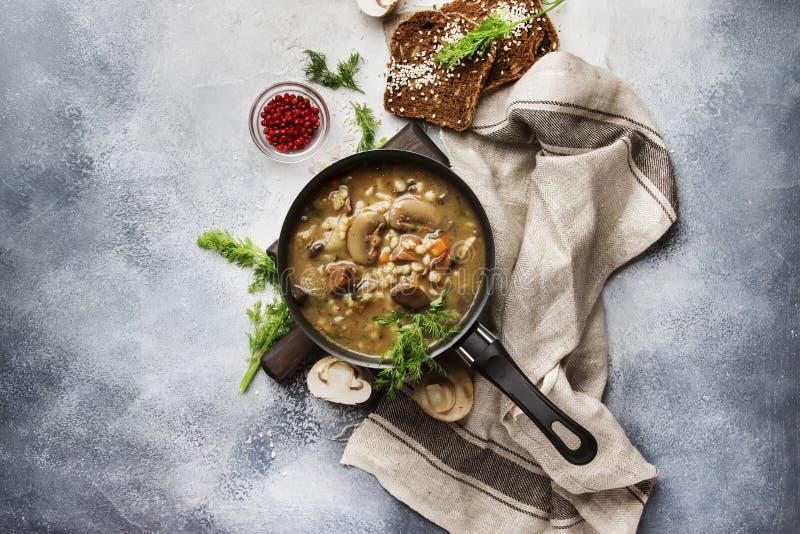 Горячий суп гриба овоща мяса с говядиной и wholegrain ячменем С черным хлебом, в лотке металла, взгляд сверху, серый кухонный сто стоковые изображения