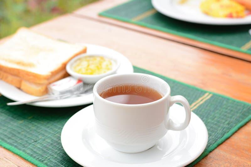 Горячий чай в белой чашке с отрезанным хлебом на зеленой циновке стоковое изображение rf