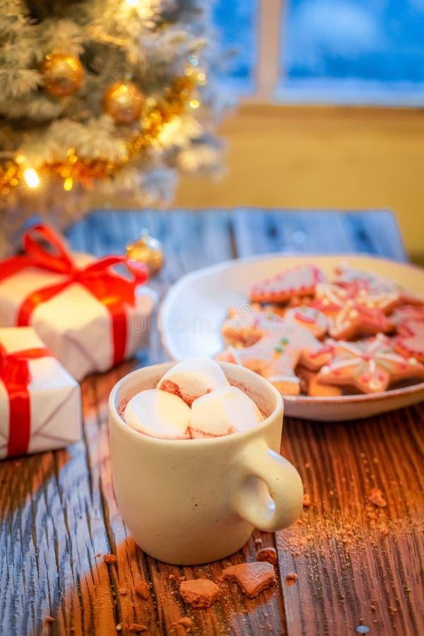 Горячий шоколад, сладостные печенья пряника и рождественская елка с подарками стоковое изображение rf
