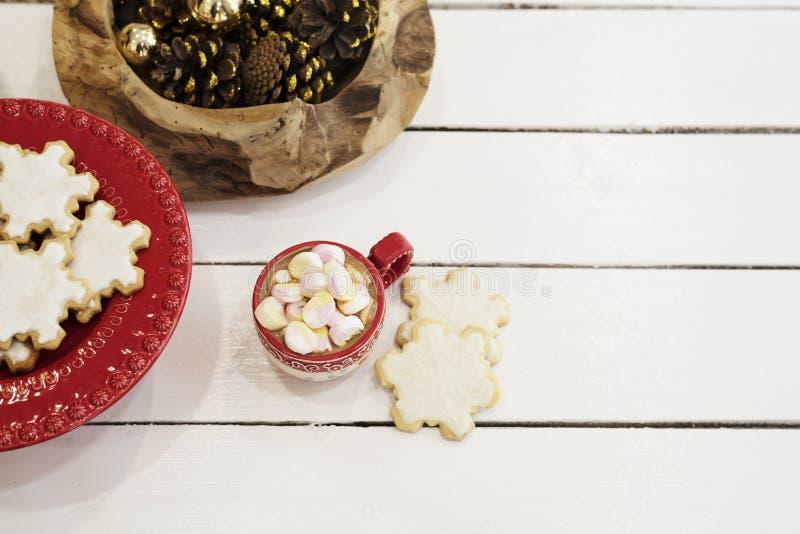 Горячий шоколад с конфетами зефира Печенья рождества сформировали в снежинках и золотых конусах деревянное предпосылки белое Взгл стоковое изображение