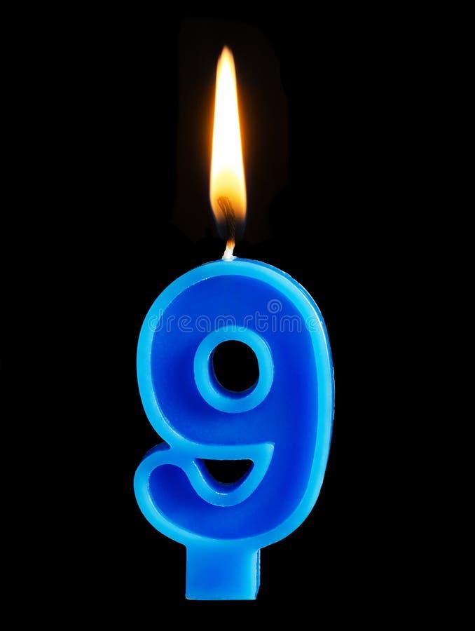Горящая свеча дня рождения в форме 9 9 диаграмм для изолированного торта на черной предпосылке Концепция праздновать день рождени стоковая фотография rf
