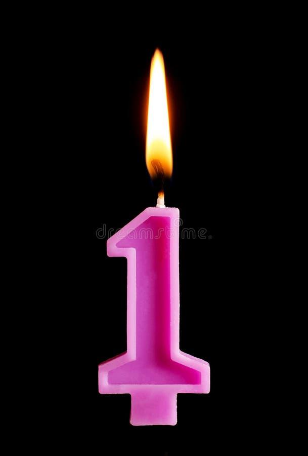 Горящая свеча дня рождения в форме 1 одного вычисляет для торта изолированного на черной предпосылке Концепция праздновать день р стоковые фотографии rf