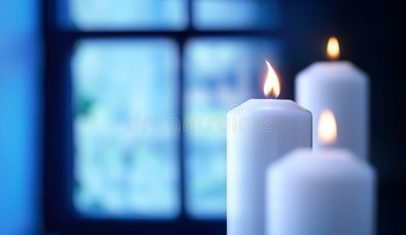 Горящая свеча перед окном стоковые изображения