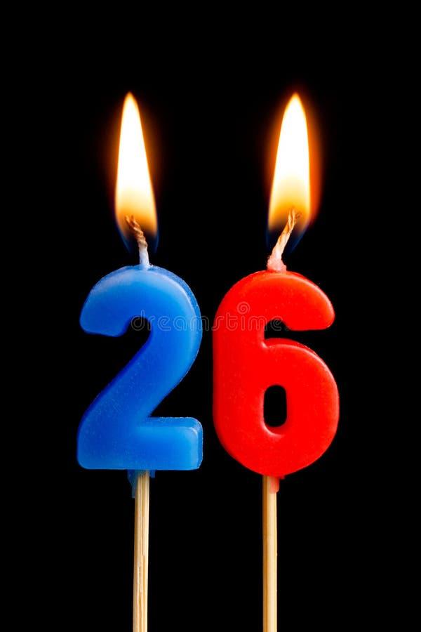 Горящие свечи в форме 26 26 номеров, дат для торта изолированного на черной предпосылке Концепция праздновать a стоковые изображения rf