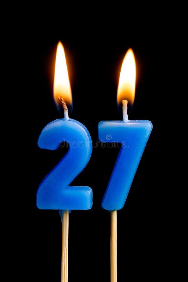 Горящие свечи в форме 27 27 номеров, дат для торта изолированного на черной предпосылке Концепция праздновать стоковое изображение