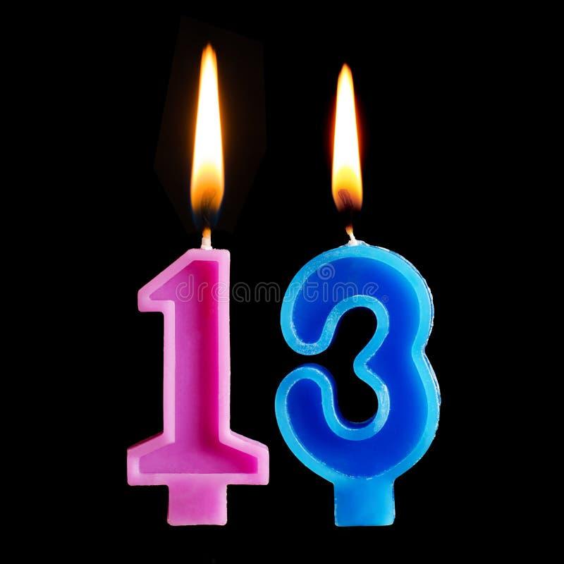 Горящие свечи дня рождения в форме 13 13 диаграмм для изолированного торта на черной предпосылке стоковая фотография rf