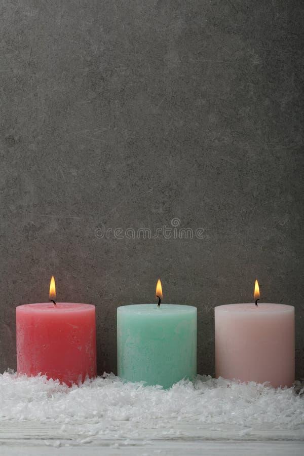 Горящие свечи цвета рождества на серой предпосылке стоковые фото