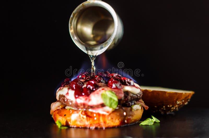 Горящий бургер полит с духами стоковые изображения rf