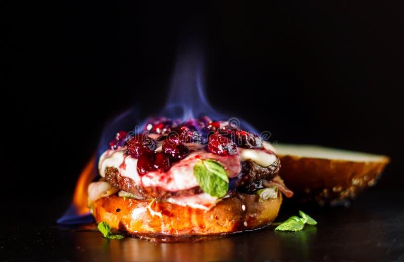 Горящий бургер, сандвич гамбургера с котлетой семенить мяса, бри сыра, камамбера, вишни ягоды Оно горит, оно стоковое изображение