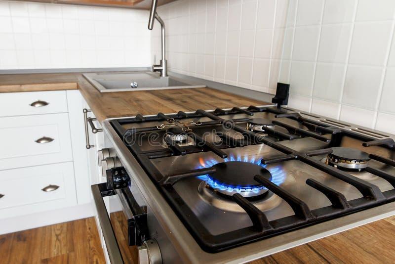 Горящий газ от плиты кухни на предпосылке стильной кухни стоковое фото