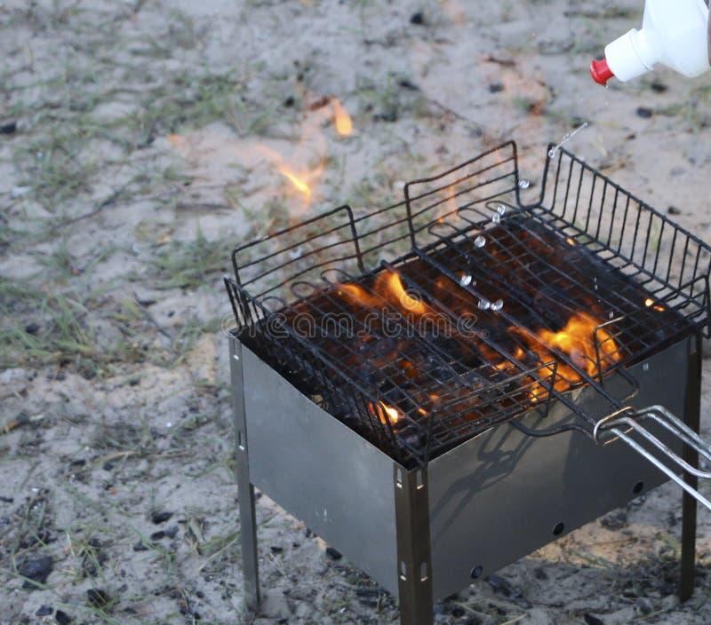 Горящий гриль на меднике с горячими углями гриль угли намочены с специальной жидкостью для сильного сгорания стоковое фото rf