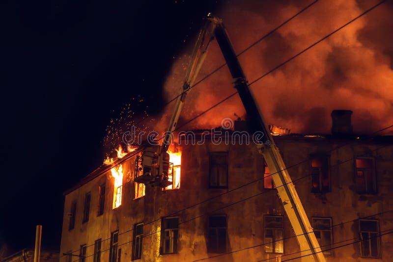 Горящий дом на ноче, крыша здания в пламенах огня и дым, пожарный на кране тушат огонь с водой от шланга стоковое фото rf