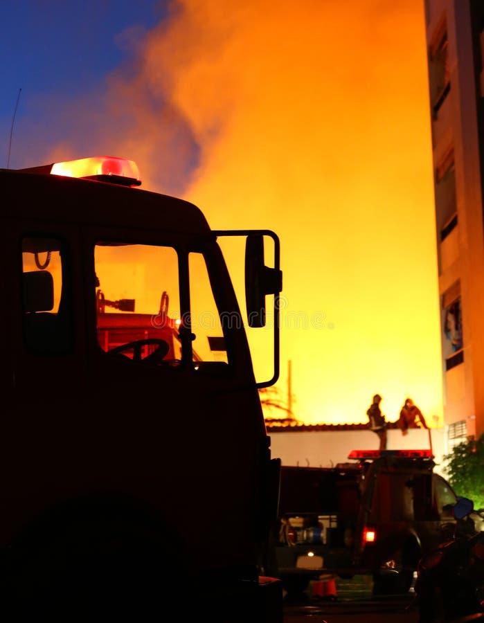 Горящий дом, пожарные пробуя потушить огонь стоковая фотография rf