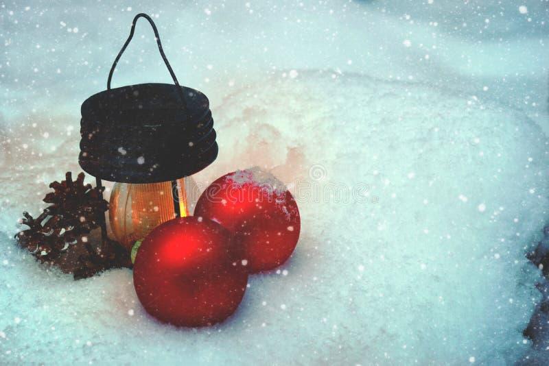 Горящий электрофонарь и украшения рождества в снеге в сугробе леса, скоро Новом Годе стоковое изображение