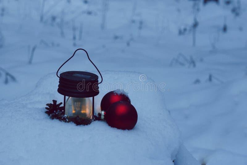 Горящий электрофонарь и украшения рождества в сугробе с twilight лесом стоковая фотография rf