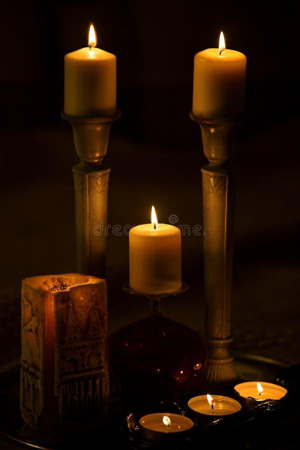 7 горящих свечей в темноте стоковое фото
