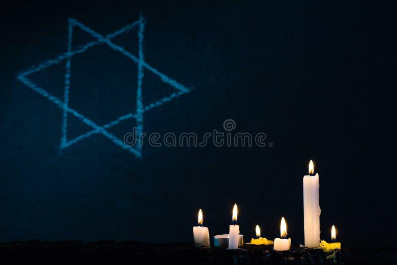 7 горящих свечей и звезда Дэвида против черной предпосылки стоковое фото rf