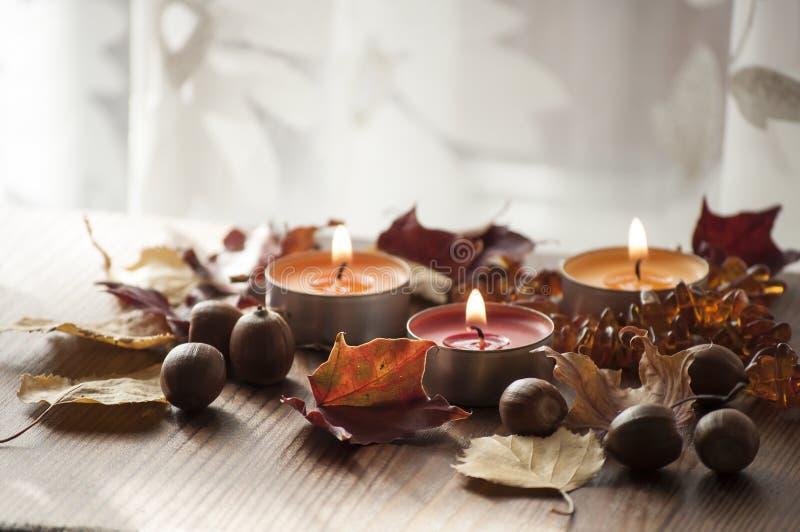3 горящих свечи, красочных листья осени и жолуди северного красного дуба и янтарного ожерелья стоковые изображения