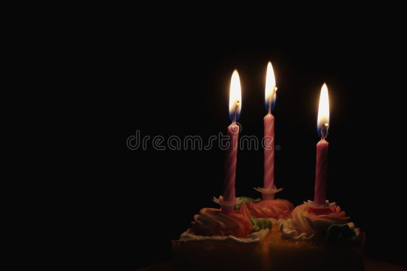 Горя свеча на торте в черной предпосылке стоковые изображения